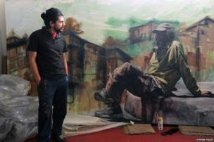 The artist and muralist Alfredo Gutierrez with his portrait of an American homeless man in Tijuana, Baja California, Mexico