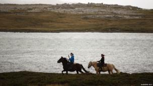 Reba Peck riding Spitfire (left) rides with the Queen's Baton with Holly Williams riding Dixie (right) in Falkland Islands.