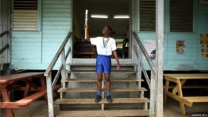 Sprinter Joy Edwards holds the Queen's Baton at Fond Assau Combined School in Castries, Saint Lucia.