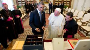 Pope Francis and US President Barack Obama exchanging gifts, with US and Church officials standing around