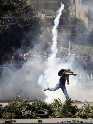 A student who supports the Muslim Brotherhood and ousted Egyptian President Mohammed Morsi throws back a tear gas canister