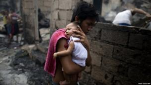 A man carries his son to an evacuation centre