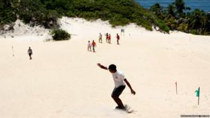 A resident surfs down the Genipabu dunes in Natal, northeastern Brazil