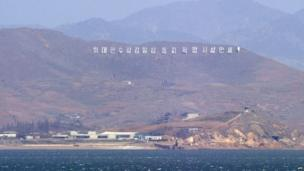 """The seafront of North Korea's west coast with signs reading """"Long live Great leader Kim Il-Sung and his revolutionary ideology!"""", is seen from the South Korea-controlled island of Yeonpyeong near the disputed waters of the Yellow Sea on 14 April 2013"""