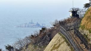 A South Korean military guard post is seen as a Navy MSB (Movement Sea Base) floats in the background at the South Korea-controlled island of Yeonpyeong near the disputed waters of the Yellow Sea on 13 April, 2013