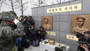 A South Korean Marine officer salutes bronze statues of two marines that were put up during a ceremony to mark the first anniversary of North Korea's deadly shelling of Yeonpyeong island on 23 November, 2011 that left four South Koreans dead