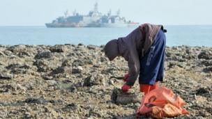 A resident gathers oyster as a South Korean Navy vessel floats in the background at the South Korea-controlled island of Yeonpyeong near the disputed waters of the Yellow Sea on 22 December, 2010