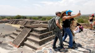Tourists take a selfie on the top of the Pyramid of the Moon