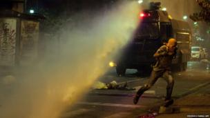 A protester runs for cover during confrontation with police in Caracas