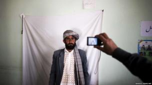 An Afghan election employee takes a picture of a resident