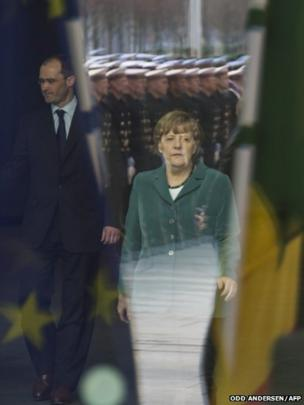 German Chancellor Angela Merkel is seen through a window while waiting for the arrival of the President of Senegal at the Chancellery in Berlin
