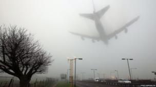 An aircraft lands in fog at Heathrow Airport