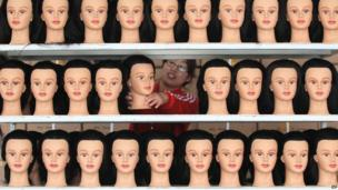A woman lines up mannequin heads