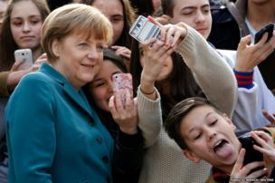 Pupils take mobile phone selfies with German Chancellor Angela Merkel