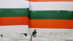 A supporter who arrived early sits awaiting the arrival of Congress party leader Sonia Gandhi at an election rally in New Delhi, India