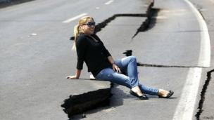 A woman poses for a picture while sitting on cracks left on a road in Iquique after the earthquake - 3 April 2014
