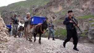Afghan election workers are escorted by armed Afghan policemen as they use donkeys to transport election materials and ballot boxes to remote polling stations in rough districts with difficult access in Kishindih district of Balkh Province in northern Afghanistan on April 3, 2014.