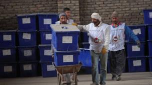 Afghan election workers prepare ballot boxes and election materials to be loaded into trucks and delivered to polling stations, at a warehouse in Herat on 3 April 2014