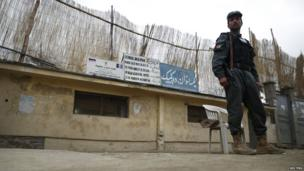 A police officer stands guard outside the Dhe Kaipaks Women's High School in Kabul on 3 April 2014