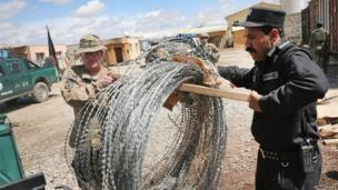 U.S. Army SFC Jeff Martin (L) from Houston, Texas helps an Afghan National Police (ANP) officer load concertina wire, which will be used to secure polling places