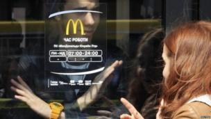 A man signals to a woman that a McDonald's restaurant is closed in Crimea's regional capital, Simferopol