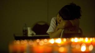 A relative of one of the passengers of the missing Malaysia Airlines plane rests in Beijing