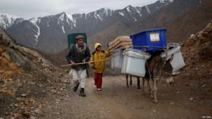 Afghans transport ballot boxes and election materials on donkeys in Panjshir province