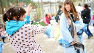 People dressed up in their pyjamas having a pillow fight