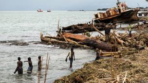 Locals walk amongst debris that was washed ashore as a result of severe flooding near the capital Honiara in the Solomon Islands in this picture released by World Vision on 6 April, 2014