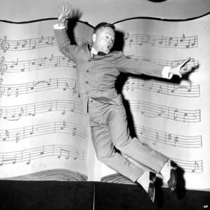 In this 1957 file photo, Mickey Rooney, wearing spats and a pinstriped suit, performs a dance routine during rehearsal for the television show George M Cohan Story in Hollywood
