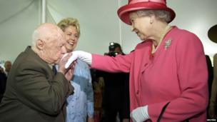 Actor Mickey Rooney kisses the hand of the UK's Queen Elizabeth II during a garden party celebrating her state visit to the US at the British embassy in Washington in May 2007