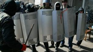 Masked activists in Donetsk prepare to confront police.