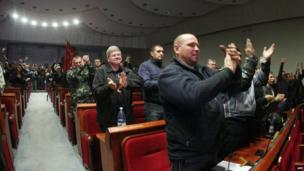 Pro-Russian activists applaud after holding in a vote in the main administration building they seized in Donetsk.