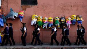 College students pass pinatas in Guatemala City