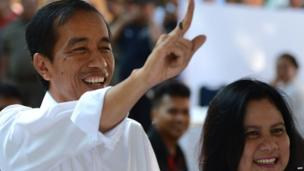 Jakarta Governor Joko Widodo and presidential candidate of the opposition Indonesian Democratic Party of Struggle (PDI-P) accompanied by his wife Iriana Widodo (R), displays his inked finger after casting his ballot during the legislative election in Jakarta on 9 April, 2014