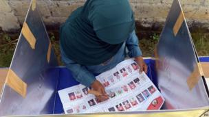 An Indonesian woman votes at a polling station during legislative elections in Jakarta on 9 April, 2014
