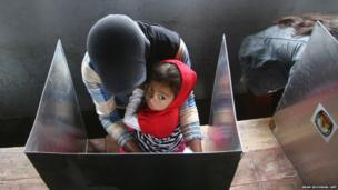 An Indonesian mother votes while carrying her child in Lumajang in eastern Java