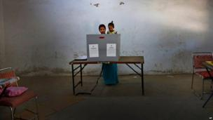 An Indian woman in Delhi casts her vote with her child in parliamentary elections on 10 April 2014