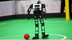 A robot representing Iran's Parand Azad University prepares to play the ball during a match against Iran's Azad University of Qazvin during the RoboCup Iran Open 2014 in Tehran
