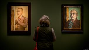A woman looks at Otto Dix's 1926 painting Self-Portrait with Easel (left) and Max Beckmann's Self-Portrait on Green in a Green Shirt (1938) during a preview for the exhibition Dix/Beckmann - Mythos Welt at the Hypo-Kunsthalle in Munich, Germany. 10 April