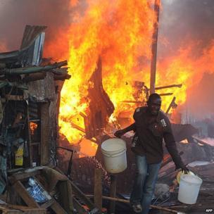 A Kenyan man runs from the scene of a fire at Deep Sea slum in Nairobi, Kenya on 9 April 2014