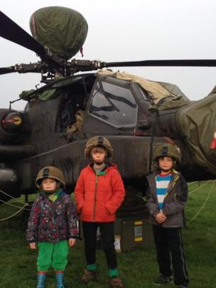 Children standing in front of an Apache helicopter