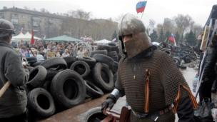 A pro-Russia activist dressed as a knight guards a barricade at the local government building they are occupying in Donetsk, Ukraine.