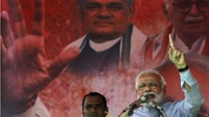 India's main opposition candidate for prime minister, the Bharatiya Janata Party's Narendra Modi addresses his supporters during a campaign rally at Balasore. Portraits in the background show former Prime Minister Atal Bihari Vajpayee, left, and senior party leader L K Advani.