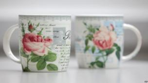 Two coffee mugs featuring a picture of a stamp with Adolf Hitler's portrait and a swastika postmark, sold by a German furniture chain after what they described as a supply-chain error.