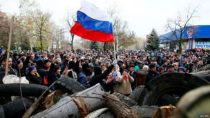 A crowd of pro-Russia protestors wave the Russian flag in front of the police headquarters in Sloviansk.