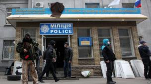 Armed pro-Russia activists guard a police station they seized in the eastern Ukrainian city of Sloviansk.