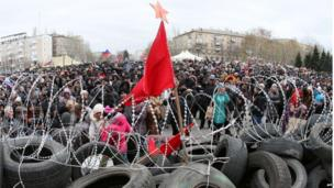 Pro-Russia supporters continue their rally in front of the regional state government building in Donetsk, with a red flag and Soviet-style red star waving above the barricade in the foreground.