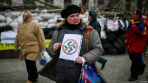 A pro-Russia protester holds an anti-swastika sign in front of a barricade outside a the regional government building in Donetsk.