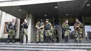 Pro-Russian armed men stand guard outside the mayor's office in Slaviansk on 14 April 2014